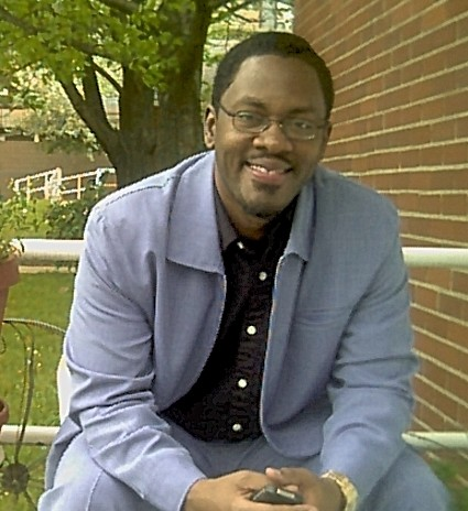 Image of a black man smiling in a professional, blue suit.